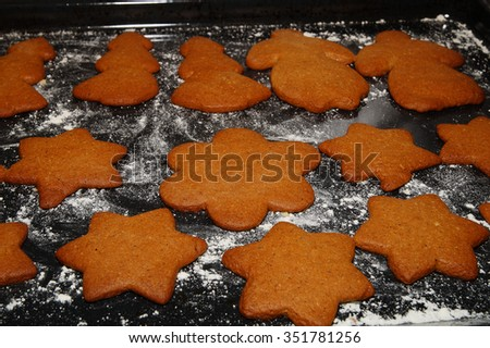 Gingerbread starts, flowers, trees and woman on a baking sheet