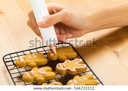 Gingerbread with icing decorating process - stock photo