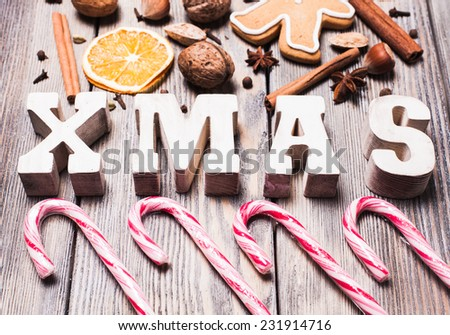 Gingerbreads with spices on the wooden table, wooden letters XMAS and Santa staffs candies. Christmas aroma decor - stock photo