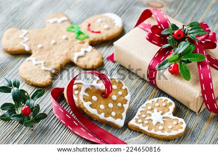 Gingerman and heart shaped cookies with icing decoration and a present box - stock photo