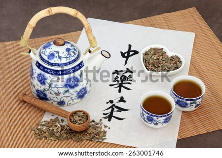 Ginkgo herb tea also used in chinese herbal medicine, with teapot, cup and calligraphy script on rice paper over bamboo. Translation reads as chinese herbal tea. - stock photo
