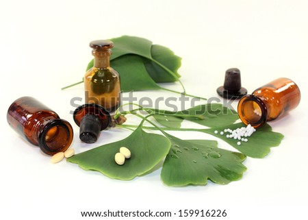 Ginkgo leaves with pharmacists bottle against white background - stock photo