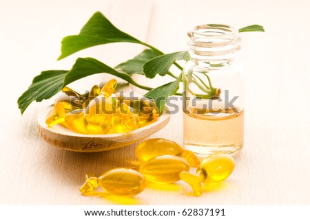 ginko biloba essential oil with fresh leaves - beauty treatment - stock photo