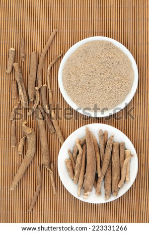 Ginseng ashwagandha herb root and korean powder over bamboo background. - stock photo