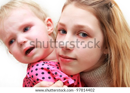 Girl - a teenager with a year-old child in her arms