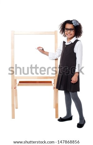 Girl about to write on whiteboard with marker pen - stock photo