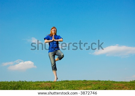Girl accepted a pose for meditation on green meadow