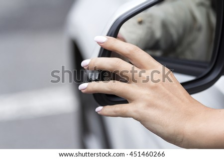 girl adjusts the rear view mirror in a white car