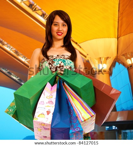Girl after shopping spree holding lots of shopping bags - stock photo