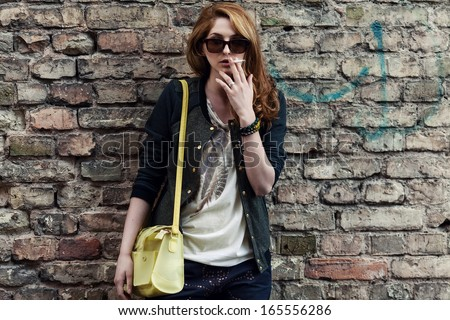 Girl against a brick wall smoking in glasses