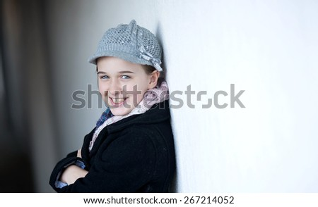 Girl against a white wall smiling with winter clothing on - stock photo