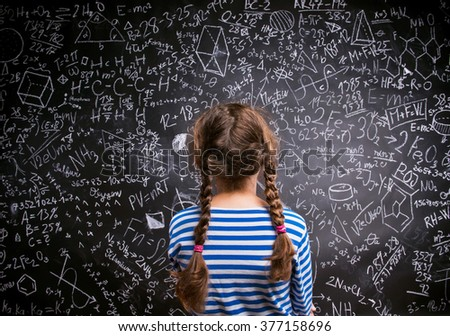 Girl  against big blackboard with formulas, back view - stock photo