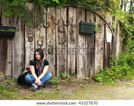Girl against the background of old wood fence with rusty horseshoes, notice paper and letter-box