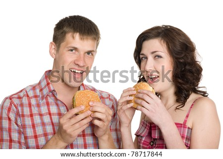 Girl and a guy eating hamburgers/ Isolated on white. - stock photo
