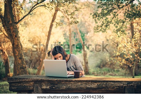 Girl and a laptop in the park - stock photo