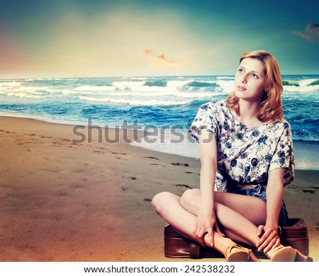 girl and a suitcase on the beach