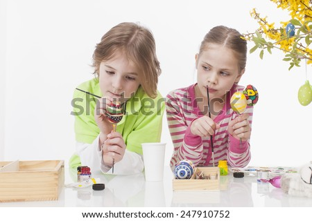 Girl and Boy colouring easter egg, smiling - stock photo