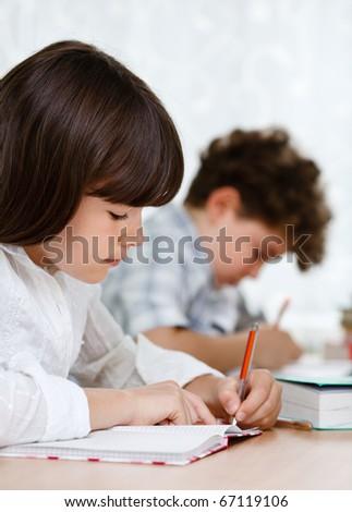 Girl and boy doing homework - stock photo