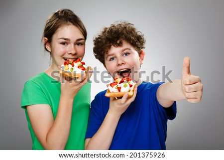 Girl and boy eating cake with cream and fruits , OK sign - stock photo