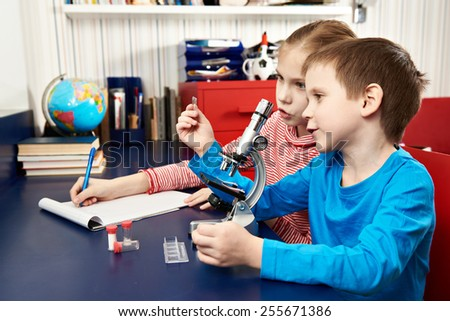 Girl and boy examines drug for the microscope for learning home table