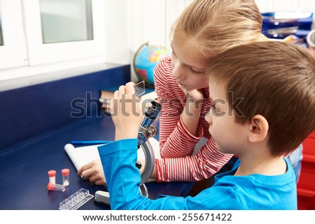 Girl and boy examines drug for the microscope for learning home table - stock photo