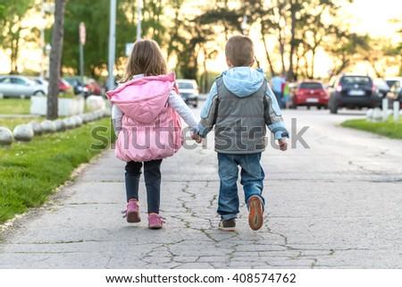 girl and boy hand in hand  running  - stock photo