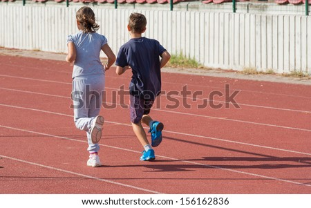 girl and boy jogging on tartan track - stock photo