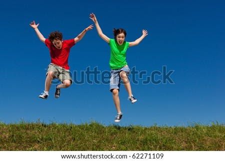 Girl and boy jumping, running against blue sky - stock photo