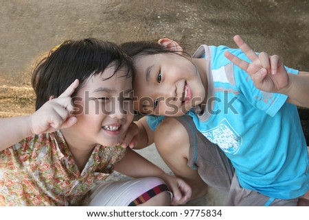 Girl and boy laughing and playing happily - stock photo
