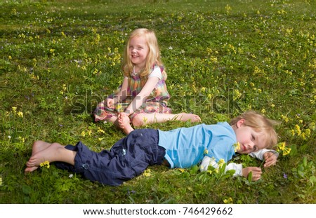 girl and boy lying in grass