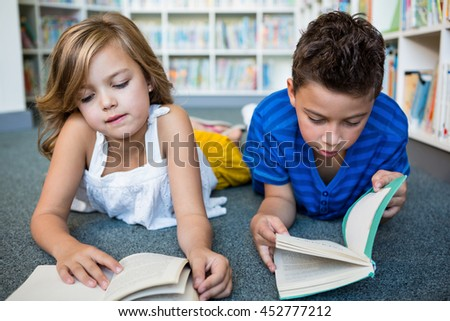 Girl and boy lying while reading books at library in school