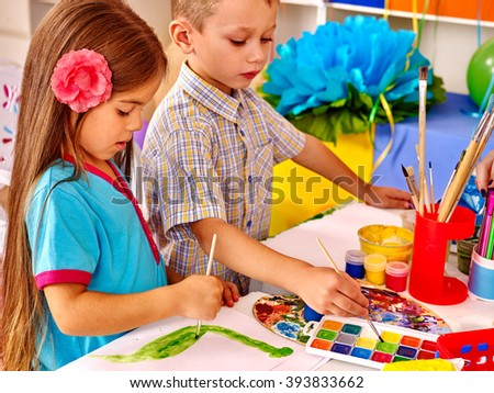 Girl and boy painting by brush on table in  kindergarten .