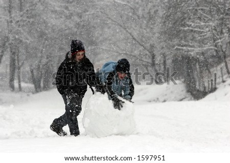 Girl and boy rolling a huge snowball - stock photo