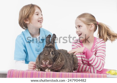 Girl and Boy with rabbit, smiling
