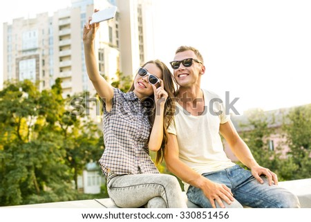 Girl and boy with sunglasses sitting outdoors at roof. They cheerfully smiling and making selfie photo on mobile phone. Nice city panorama