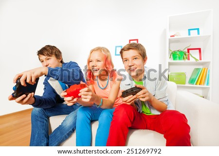 Girl and boys with joysticks playing game console - stock photo
