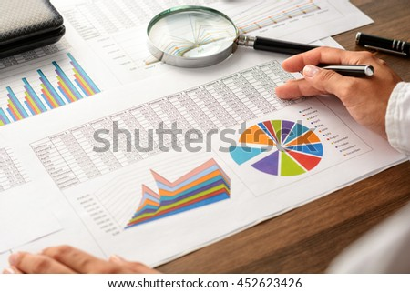 Girl and business accessories (notebook, calculator, planchette, tablet, fountain pen, glasses) and graphics, tables, charts on white sheets on office desk. Soft focus.