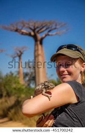 Girl and chameleon in the Avenida de Baobab in Madagascar - stock photo