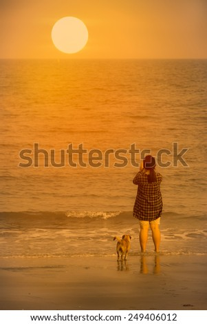 Girl and dog on the beach. - stock photo