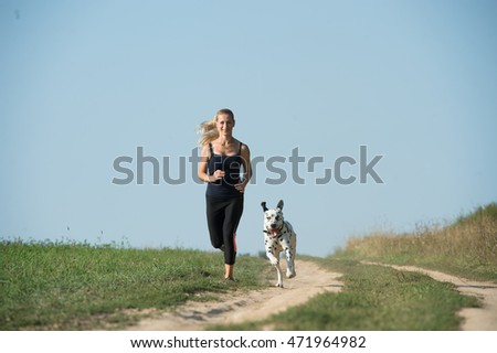 Girl and dog running on the field