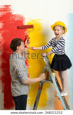 Girl and father fooling while painting wall in bright colors. Girl in hard hat standing on stepladder painting dadys nose - stock photo