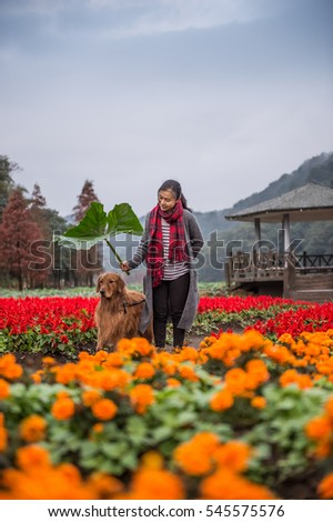 Girl and golden retriever in the flowers