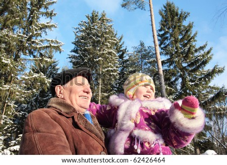 girl and grandfather in winter forest - stock photo