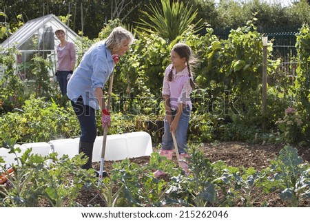 Girl and grandmother digging in garden, smiling, mother standing beside greenhouse, watching