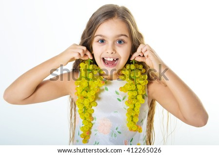 Girl and grape. Beautiful girl holding two bunches of grapes. Girl playing with grapes, cheerful girl eating grapes