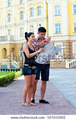 Girl and guy with map on street. - stock photo
