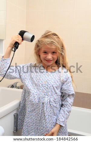 girl and hairdryer in the bathroom - stock photo