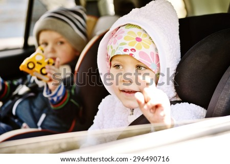 girl and her brother  traveling in baby car seats - stock photo