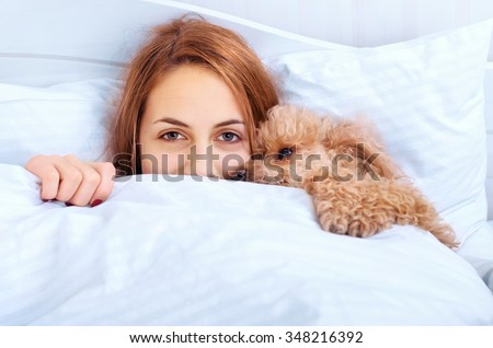 Girl and her dog in the bed - stock photo