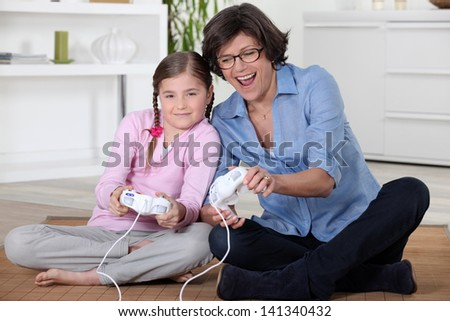 Girl and her grandmother playing computer games - stock photo